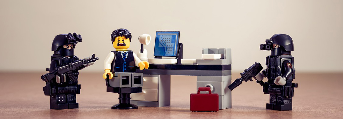 Shown are three Lego figurines to illustrate that you are subject to penalties if you fail to comply with GDPR. In this image, the figurine in the middle is a mustachioed businessman seated in front of a computer atop a desk. He looks terrified. Flanking him are Lego figurines made up to look like armed members of a SWAT team. They wear black uniforms and helmets with night-vision goggles attached. One holds an assault rifle, while the other holds a pistol with a silencer attached.