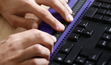 This image shows hands placed atop a Braille keyboard.